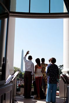 President Barack Obama and First Lady Michelle Obama wave to the crowd from the…