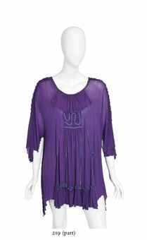 Marc Bolan   A short sleeved tunic top of purple silk jersey, labelled Zandra Rhodes, London, with smocked panel at front and back embroidered with a turquoise wave motif, slashed design and 'lettuce' edging in turqoise, owned and worn by Marc Bolan in the 1970s, including during recording sessions for the album Tanx at the Chateau d'Herouville, France, October 1972; accompanied by an EP Bolan's Best +1, the sleeve featuring a black and white photograph of Bolan wearing the tunic on stage…