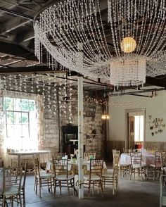 Industrial chic with rented vintage table décor | crystal wedding chandelier | hanging paper ceiling decoration | mismatched table setting wedding reception | Sundance Studios Vintage Events