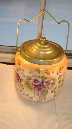 """Really nice English China Biscuit Jar with Brass lid and handle. Beige with green leaves and mauve and bronze flowers. I date this to 1920's but it could be earlier. Measures: 5 3/4 """" with Lid, Width is 5 3/4"""" approx.   eBay!"""