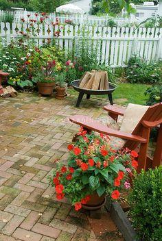 Backyard Brick Patio, Firepit, Red Adirondack Chair, Pots Of Annuals,  Perennials,
