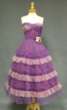 A charming 1950's prom dress in lavender and violet tulle. Strapless, heart shaped bodice with pleated bust. Dress has a full, ruffled skirt. Boned. Lined. Side metal zipper.