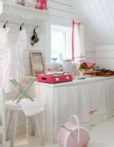 sweet corner play kitchen for a lucky little girl, looks like it;s set up on 1 long shelf with a skirt. great idea without building the unit. just add tabletop stove, cut hole for sink, drop a dishpan in-creative idea for building-challenged!