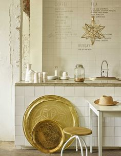 White kitchen with raw walls and golden details