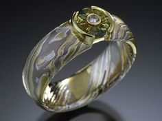 Comfort fit engagement ring that is 6mm wide in mokume of etched 18K yellow gold, 14K palladium white gold and sterling silver with 18K yellow gold open half bezel. Shown with TorusRing sapphire with tube set diamond in the sapphire.
