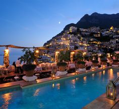 Le Sirenuse pool terrace is full of flowers and lemon trees overlooking the sea in Positano, Italy.