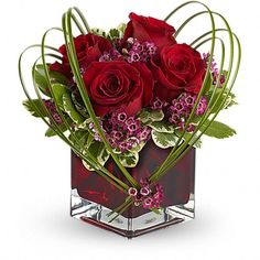 Sweet Thoughts Bouquet with Red Roses  Price:  US$39.99  If youd like someone to think sweet thoughts about you, send them this delightful bouquet! A graceful heart of bear grass is tied with purple waxflower, and appears to float above red roses nestled in a ruby-red glass vase. How sweet it is!