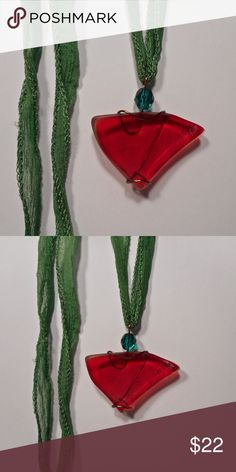 "vintage red glass holiday necklace pendant Dark red vintage glass, crafted into a pendant necklace by wrapping with bronze plated wire. Adorned wth a faceted green glass bead. Comes on a green fairy silk ribbon. 1 3/4""h x 1 7/8""w. Perfect holiday accessor"