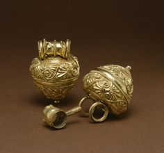"""Hollow pendants like these, called """"bullae,"""" contained protective charms or perfume and were worn as amulets, especially by children. A stopper at the top, held in place by a chain or cord, secured the contents. The heart-shaped bodies of these Etruscan """"bullae"""" are decorated with detailed palmettes and tendrils worked in repoussé and has intricate smooth and twisted wire applied to the surface. Etruscan, 5th century BC"""