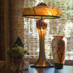 Graceful Luster Art Glass table lamp with a Cherry Blossom design and matching vase is hand blown by renowned glass artisan Carl Radke. Each lamp and vase is signed and dated by Radke to assure authenticity and to retain its future collector value. #myOCLlight #oldcalifornia #oldcalifornialighting #craftsmanlighting #madeinamerica #solidbrass #artsandcrafts #lusterglass #tablelamp