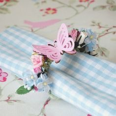 Paper flowers twisted into napkin holders, with hand painted wood and paper punched butterflies.