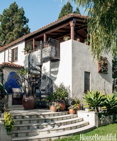To enhance the hacienda-inspired architecture and connect the upper terrace with the patio in a Santa Monica California house designer David Dalton designed a wrought-iron staircase. The barbecue's backsplash features tiles from Mission Tile West. Spanish Style Homes, Spanish Revival, Spanish House, Spanish Colonial, Renaissance Espagnole, L'architecture Espagnole, Style Hacienda, Design Exterior, Exterior Homes