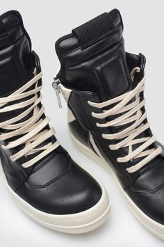 RICK OWENS Geobasket High Top Sneakers. Black lace up high top sneakers. Off-white sole and laces. Zipper closure. Upper: 100% Calf Leather Sole: 100% Rubber Made in Italy