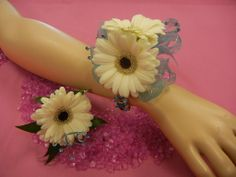 Flowers By Frances: White gerbera dasies, light blue quintetts, light blue wire accents, light blue ribbon, and a jewelled wristlett. Corsage and matching boutonniere designed using customers ideas.