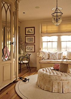 Dressing room with window bench, round rug, overscale tufted ottoman, and built-in armoire designed to look more like furniture; interior design by Barry Dixon #armoire #dressing_room #mirrored #wardrobe