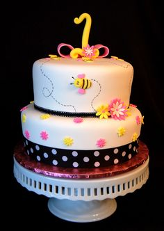 Bumble Bee 1st brthday cake - Fondant covered bumble bee themed birthday cake, with black ribbon and pink and yellow daisies.