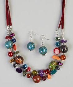 This fresh and joyful necklace features an array of nature-inspired beads strung on sleek silver-tone strands and classic coding. Coordinating earrings lend the lobes sophisticated shine.