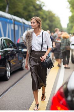 Chocolate leather midi skirt with a white button down, flat sandals, and a Proenza fringe bag.