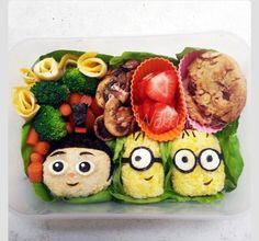 Minion bento. Agnes is made from rice ball colored with soy sauce and details from nori and egg white. Minions are made from rice ball colored with turmeric and details from nori and egg white. Cookies represent the Cookie Robot from the first film.
