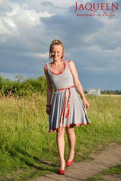 Edles Sommerkleid aus super weichem, elastischen Viskosejersey. Das Kleid ist hellgrau, Bündchen und Gürtel sind mit einem rot/orange/weiß geblümte...