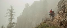 REI Expert Advice: How to Go Backpacking in the Rain - two backpackers hiking in the rain
