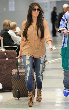 Kim Kardashian wearing Siwy Hannah Ankle Skinny Jeans in Tempest, Louis Vuitton Pegase Rolling Suitcase in Damier Canvas, Tom Ford Nicole Sunglasses, Christian Louboutin Lipspikes Boots in Leoprad and Zara Blouse with Pleated Shirt Front.