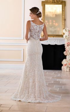 From Stella York, this all over lace column wedding dress features a classic silhouette with an updated shape. Embroidered lace over Dolce satin is done in a simple way that makes a big impact. The neckline and lace straps are adorned with beading that highlights the bride's face. Beautiful lace in a rose motif covers the sheer back and and continues into the soft train. An easy zip-up back under fabric covered buttons finishes this simple yet elegant bridal look.