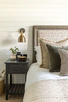 A neutral scheme with wall lamp showing how to make a small bedroom look bigger.