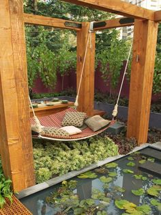 Suspended from a massive rustic pergola over a verdant garden bed, this oasis designed by Jamie Durie features a generously sized hammock, perfect for napping next to the adjacent miniature lily pond or languidly conversing with guests at the dining table on the other side. Click through for more outdoor bedrooms and outdoor decorating ideas.
