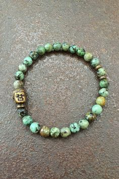 This bohemian bracelet is beaded with gorgeous African Turquoise and bronze beads featuring a detailed Buddha bead. Great neutral colors to blend with any outfit...  Measures: Inner circumference 6.75 inches, size medium stretch bracelet.  I use only top quality beads and lead/chromium free leather in my work. Thanks for visiting...