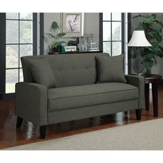 This charcoal gray linen sofa adds a warm, cozy touch to your living space. Covered in durable linen-looking fabric, the sofa features a button-tufted back, tapered wooden legs with an espresso finish, and comes with two matching throw pillows.