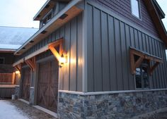 The exterior of house- vertical siding with stone veneer