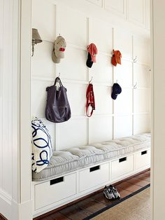 Evenly spaced hooks and an ultra comfy bench cushion make this once-crammed entryway open and inviting. Bins beneath the built-in bench provide hidden storage, while a wall of wainscoting gives the area upscale style.