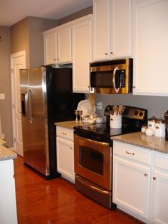 Kitchen: stainless steel, white cabinets, gray wall