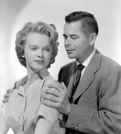 Medium publicity shot of Anne Francis as Anne Dadier with Glenn Ford as Richard Dadier, holding her shoulders.