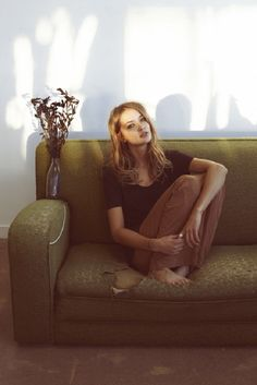 blonde // girl // sitting on a green couch // modern sofa // sunlight // portrait // thoughtful