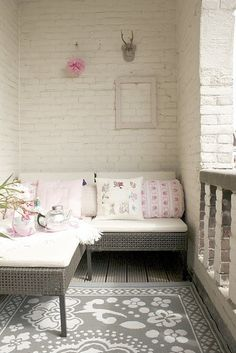 Absolutely LOVE this idea for a cozy nook on a deck.  The colors are amazing with the white brick.  Wonderful!
