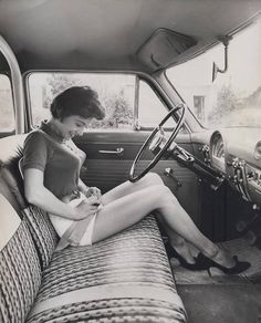 Girl with early car seat belt, ca. 1950s.
