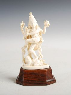 Lot 672 - A late 19th/ early 20th century Indian ivory figure of Shiva, on carved wood plinth, 15.5cm high.