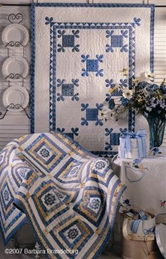 blue and white. great way to layer quilts! wall hanging!! one over the table and then drape another quilt over a chair. But start first w/quilts (cutters of stackers, you can hide the holes/stains) on the wall