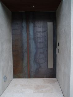 corten steel door + concrete wall + stainless steel handle