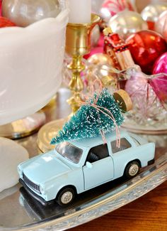 Sweet vintage-style toy car with a Christmas tree tied to the top.