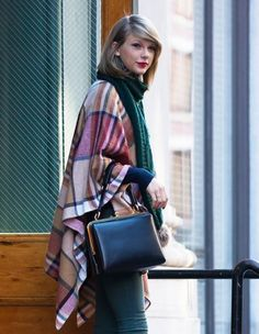 Taylor Swift keeping warm in this New York chic outfit: plaid poncho, green scarf, ladylike top-handle purse, and signature crimson lips.