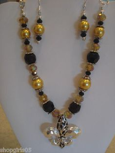NEW! FLEUR DE LIS NECKLACE AND EARRING SET. COLOR ARE BLACK AND GOLD. WOULD LOOK GREAT WITH YOUR OUTFIT AT THE NEXT GAME. BEAUTIFUL!!