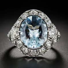 Art Deco Aquamarine and Diamond Ring. A refreshing splash of cool blue sparkles from the center of this unusual, impressive and thoroughly stunning aquamarine ring, hand fabricated in platinum - circa 1920s-30s. The glistening 4.55 carat gemstone is embraced all around with 1.35 carats of bright-white European-cut diamonds glittering from within mostly individual honeycomb style settings.