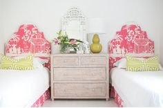 Palm Beach style bedroom design featuring a pair of coral pink arched pink toile upholstered beds with matching skirts