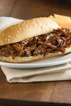 Slow cooker pulled pork recipe is flavored with hickory & brown sugar barbecue sauce before serving in French rolls