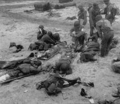 Medical personnel attend to wounded members of the 2d Naval Beach Battalion on Utah Beach. 1st Engineer Special Brigade people can be seen in the background. The photograph is believed to have been taken near Exit 2, Utah Beach, 6 or 7 June 1944. Source: US National Archives http://med-dept.com/gallery/treatment-of-wounded/