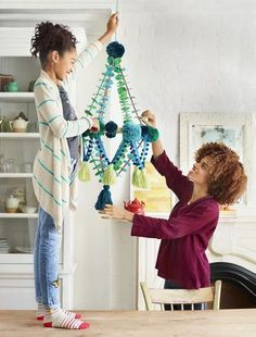 """We're obsessed with pajaki (""""pie-yonky"""") chandeliers! This Polish craft, traditionally made with colorful paper flowers, is the perfect foil for gray winter days. Spend a few hours helping your child make our woolly version with yarn and felt, and you'll both feel brighter!"""