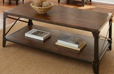 Distressed tobacco wood and metal coffee table with antiqued metal x side leg accents lower storage display shelf matches numerous decor styles Industrial, Rustic and Southwestern.